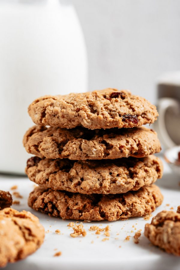 stack of 4 oatmeal raisin cookies with milk in the background