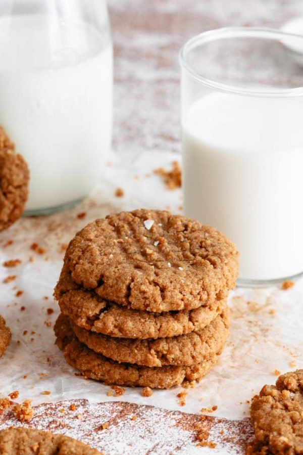 small stack of vegan peanut butter cookies next to a glass of milk