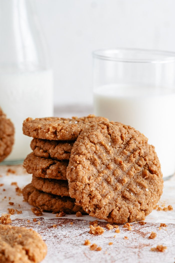 stack of vegan peanut butter cookies next to a glass of milk