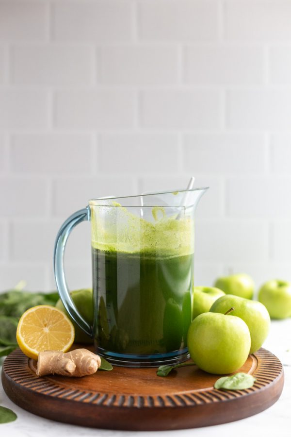 pitcher full of freshly squeezed green juice on a wood board with a white background