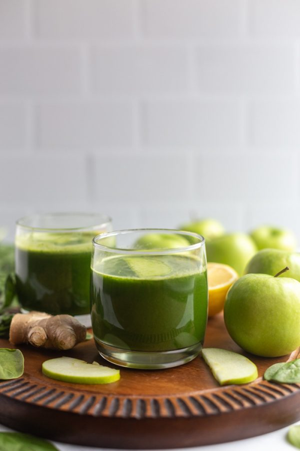 cups of green juice on a board with apples and fresh ginger