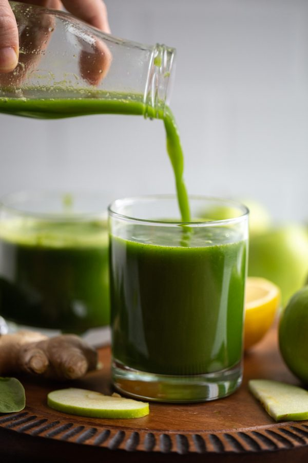 Apple green juice being poured into a small glass on a wood board
