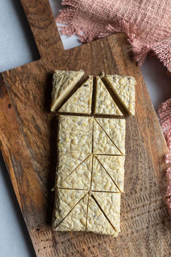 block of tempeh on top of a wood board and cut into little triangles