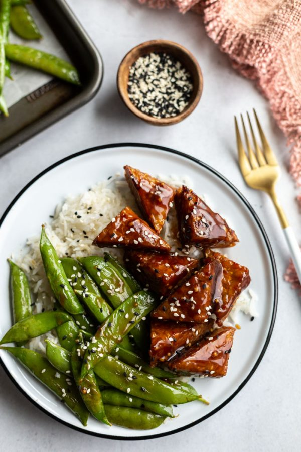 smoked tempeh pieces and sugar snap peas on top of white rice in a bowl and sprinkled with sesame seeds