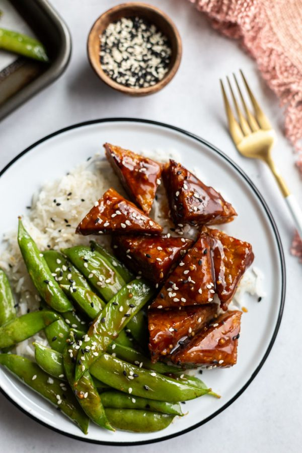 smoked tempeh and sugar snap peas on white rice in a white bowl