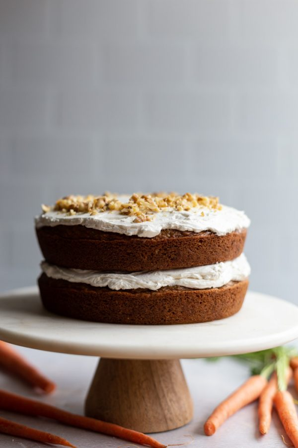 iced carrot cake on a cake stand with carrots around it
