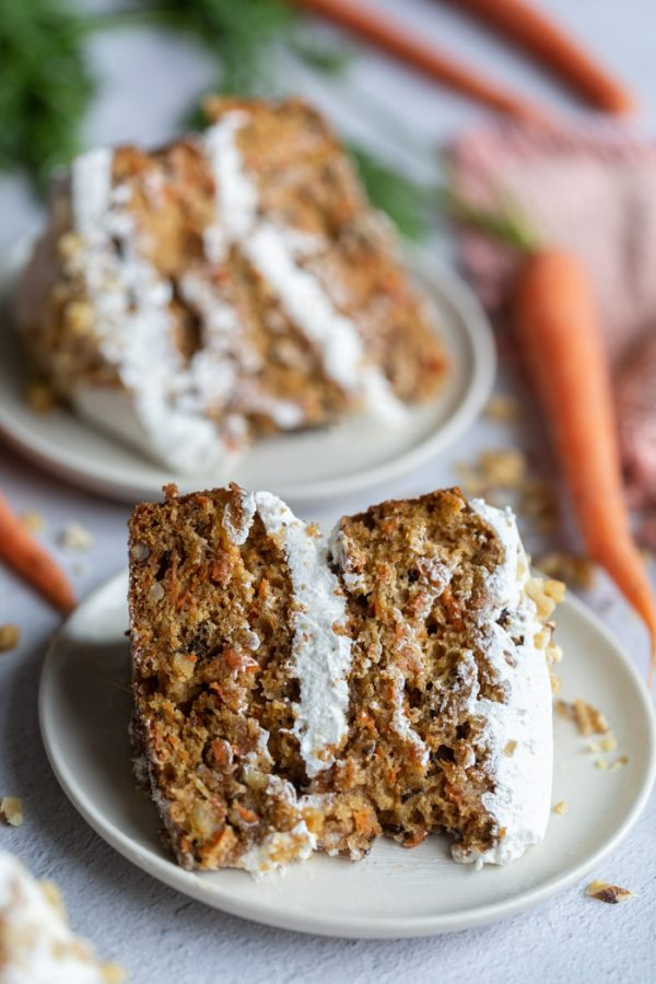 2 slices of vegan carrot cake with frosting on top
