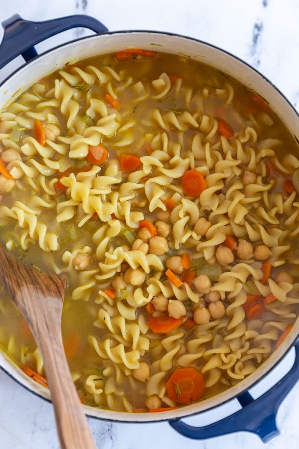 chickpea noodle soup with carrots in a large pot