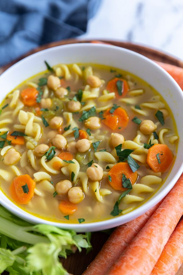 chickpea noodle soup surrounded by fresh vegetables