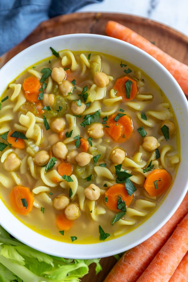 chickpea noodle soup with carrots on a wooden board