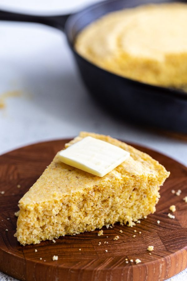 slice of cornbread on a wood board with a slice of butter on top