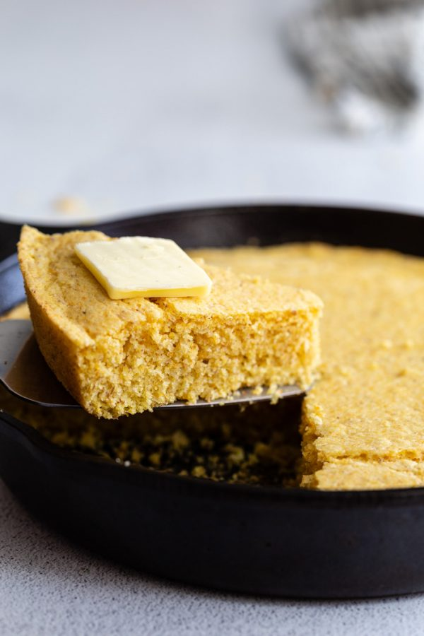 slice of cornbread on a spatula being pulled out of a skillet with butter on top