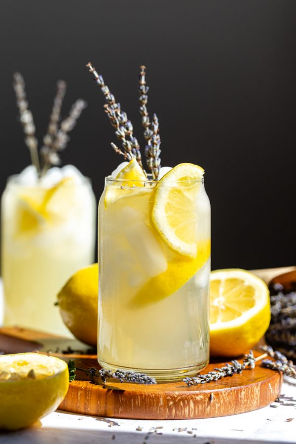 glass of lemonade with slices of lemon and lavender in it. sitting on a wood board with a black background