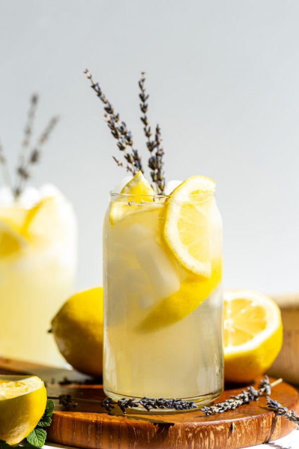 glass of lemonade with slices of lemon and lavender in it. sitting on a wood board with a white background
