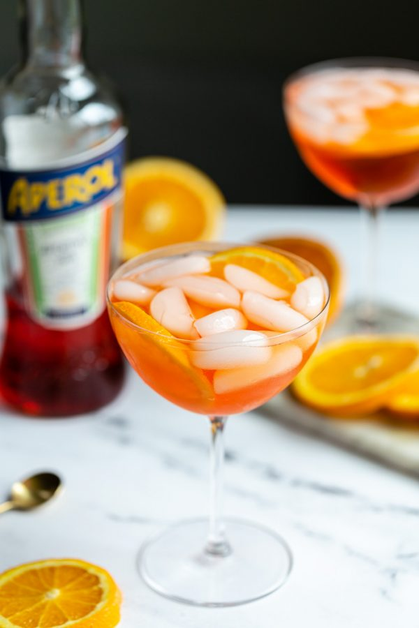 orange cocktail in a wine glass on a marble backdrop with oranges all around and a bottle of aperol in the background