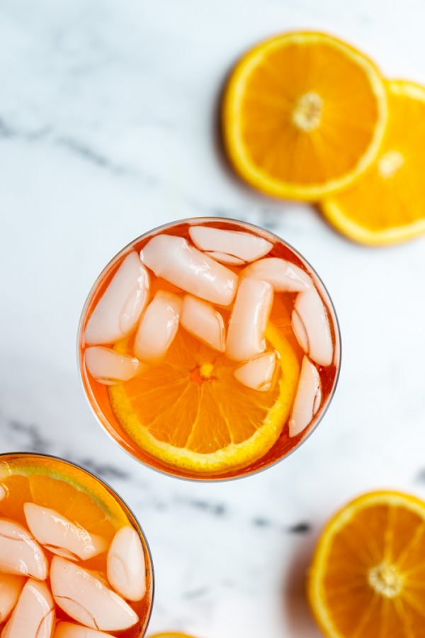 orange cocktail in a wine glass on a marble backdrop with oranges all around