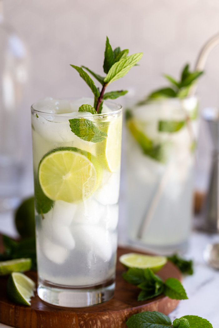 2 mojitos in tall glasses with fresh limes and mint in them. Sitting on a round wood board with a light tile background