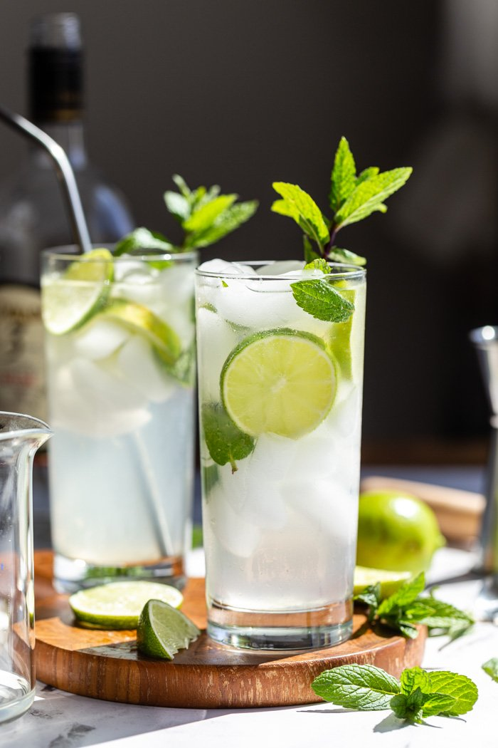 2 mojitos in tall glasses with fresh limes and mint in them. Sitting on a round wood board with a dark background