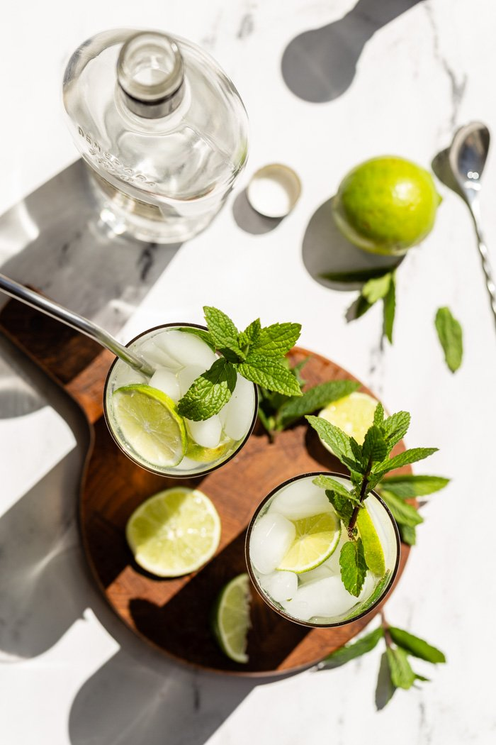 top down shot 2 mojitos in tall glasses with fresh limes and mint in them. Sitting on a round wood board