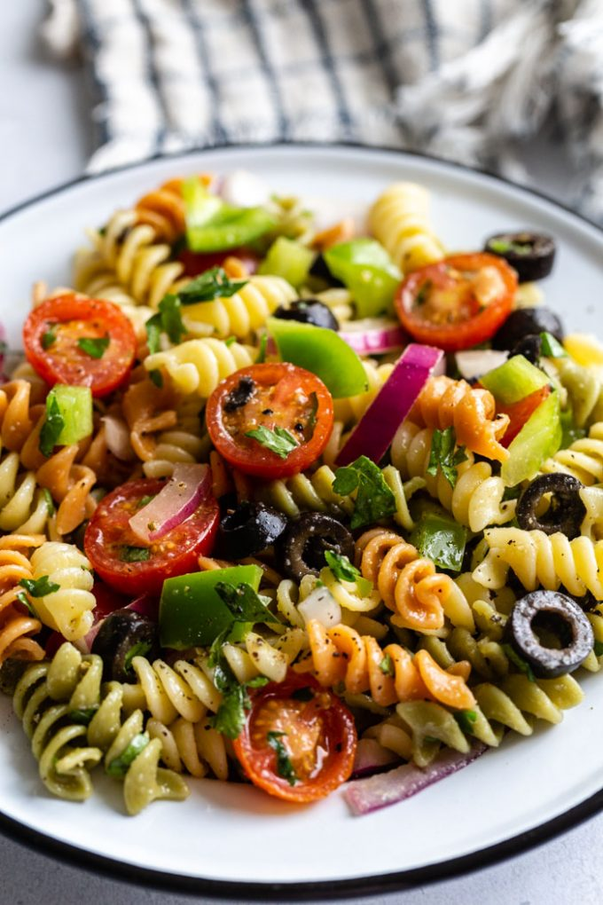 close up shot of pasta salad with tri color past spirals and veggies