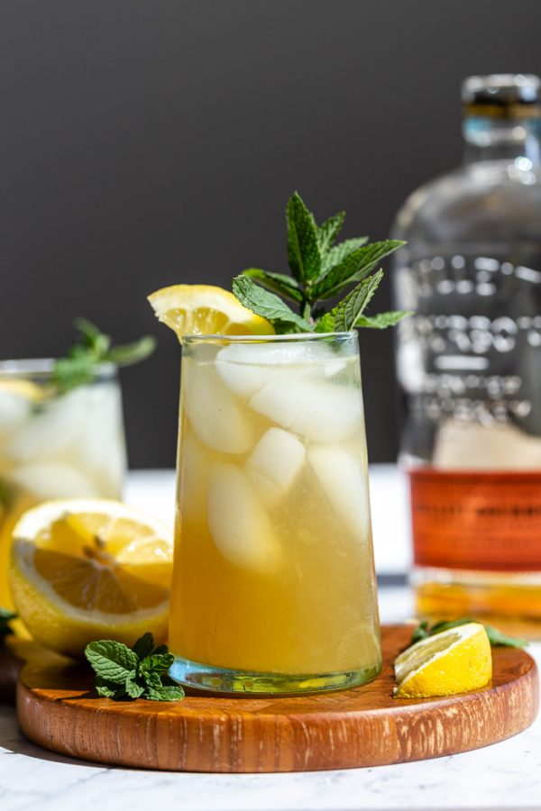 yellow/ orange whiskey cocktail on a wood board with lemon and mint popping out the top and a bottle of bourbon in the background