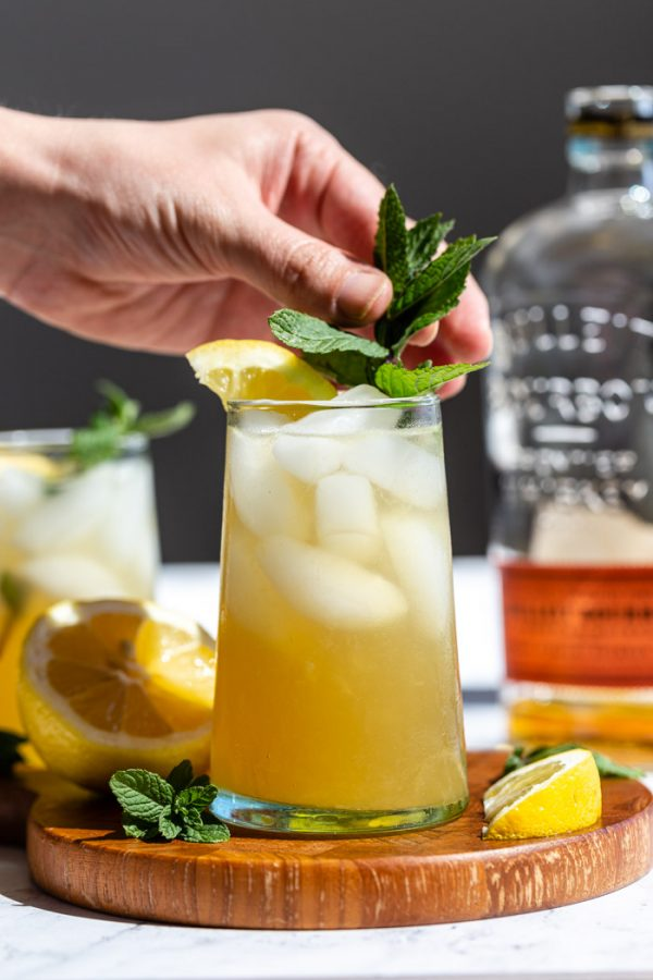 yellow/ orange whiskey cocktail on a wood board with lemon popping out the top and a bottle of bourbon in the background. a hand place a sprig of mint into the cocktail