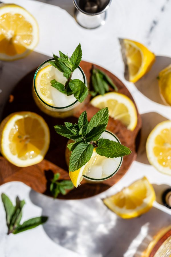 top down shot of 2 whiskey cocktails with lemon and mint all around on a round wood board
