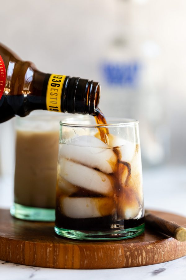 small cup of a white russian: black liquid on ice with kahlua being poured into the glass