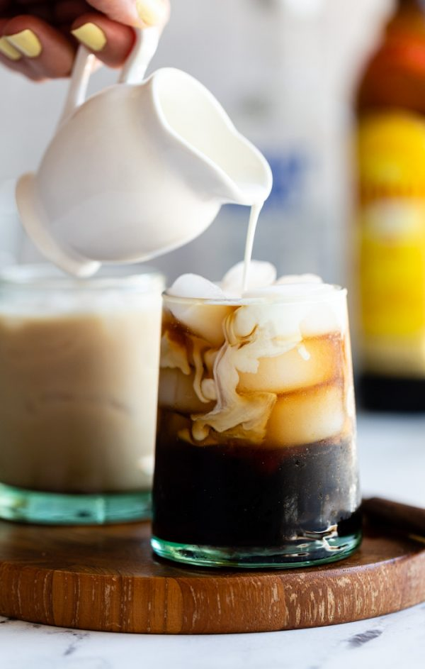 small cup of a white russian: black liquid on ice with cream being poured into the glass