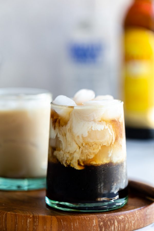 small cup of a white russian: black liquid on ice with cream floating at the top of the glass. on a wood board with white background