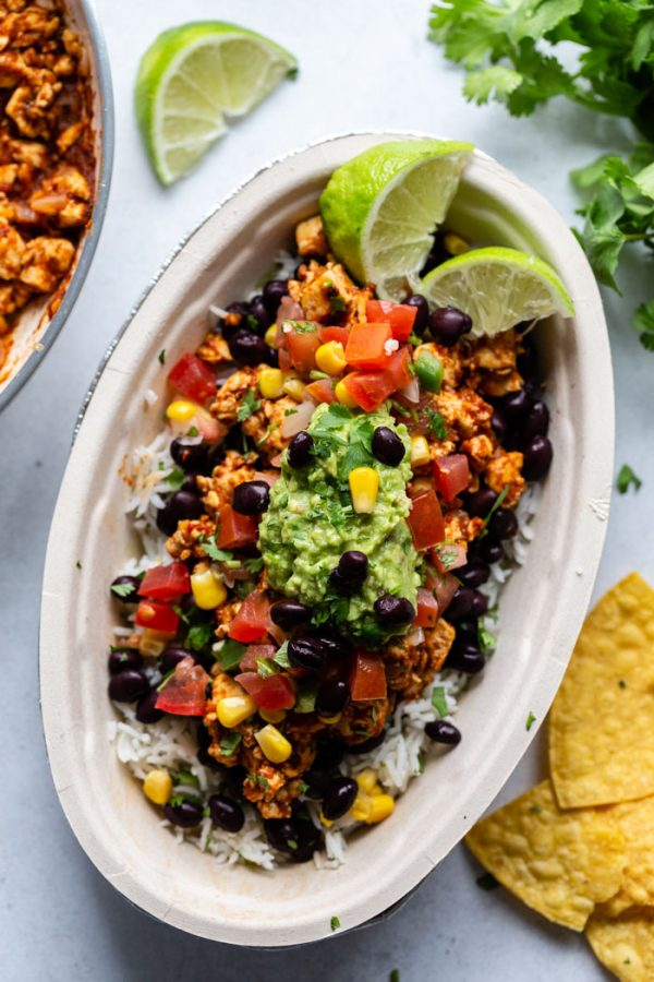 chipotle burrito bowl filled with rice, black beans, salsa, corn, tofu sofritas, lime wedges and topped with a spoonful of guacamole. on a white bowl with cilantro and chips around the bowl