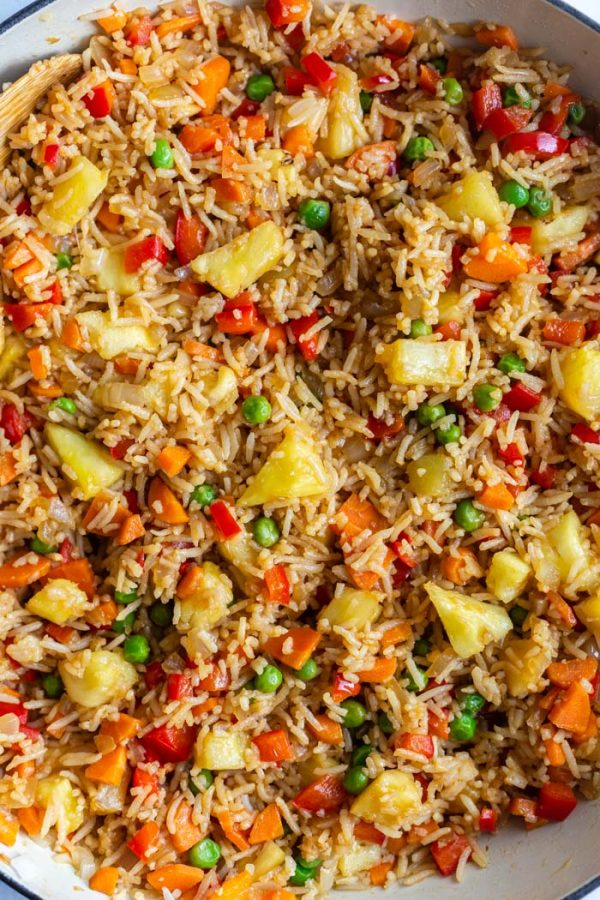 top down shot of fried rice in a large skillet with peas, pineapple, red bell pepper, and carrot