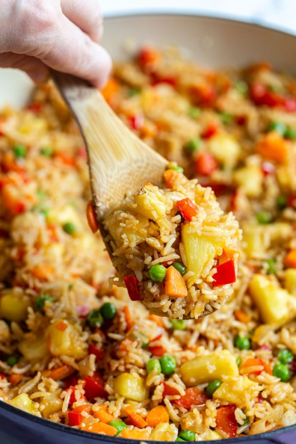 shot of fried rice in a large skillet with peas, pineapple, red bell pepper, and carrot. a scoop of the rice is being taken out