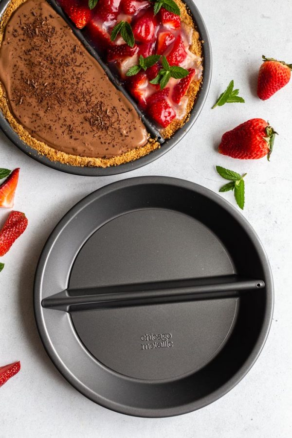 """double sided """"split decision pie"""" with a chocolate silken pie on one side and a fresh strawberry pie on the other. Fresh strawberries and mint are around the edges of the frame. this image shows a full pie dish and an empty one"""
