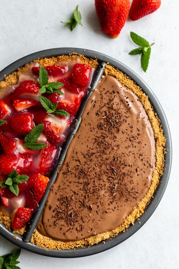 """double sided """"split decision pie"""" with a chocolate silken pie on one side and a fresh strawberry pie on the other. Fresh strawberries and mint are around the edges of the frame"""
