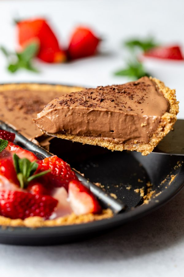 """double sided """"split decision pie"""" with a chocolate silken pie on one side and a fresh strawberry pie on the other. Fresh strawberries and mint are around the edges of the frame. This image shows an up close shot of a piece of chocolate pie coming out of the dish"""