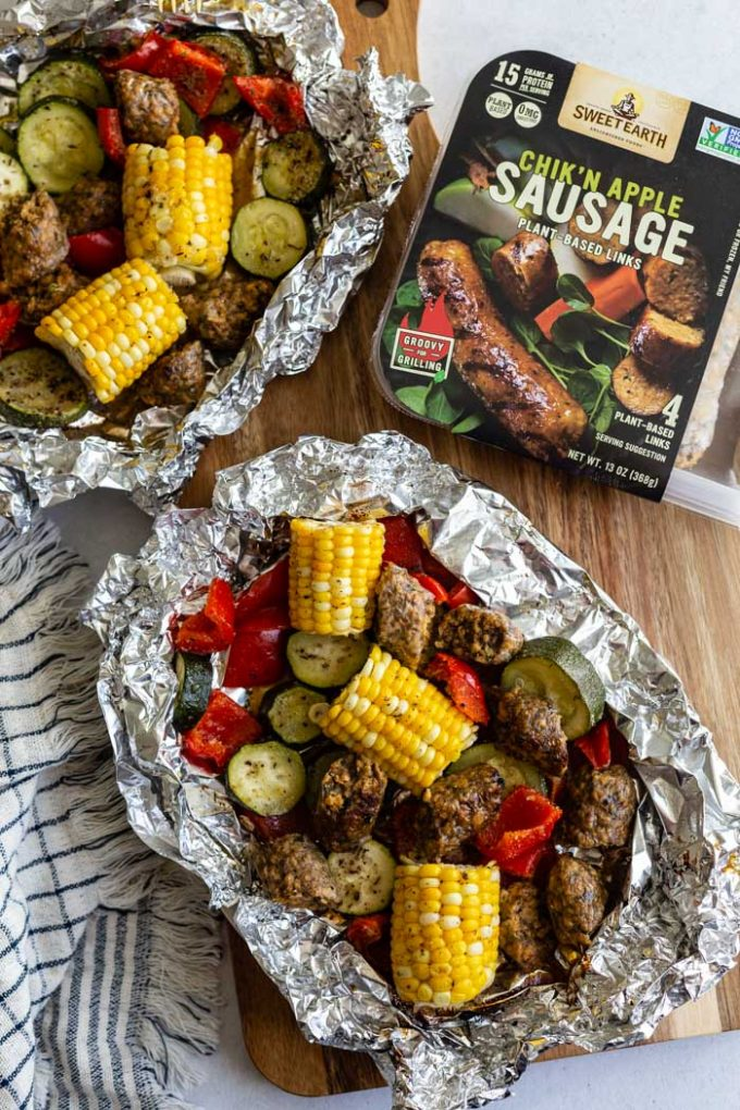 foil pack filled with vegan sausage, corn on the cob, bell pepper and zucchini. pack is sitting on a wood board with a towel in the corner. also the sweet earth brand packaging in the corner