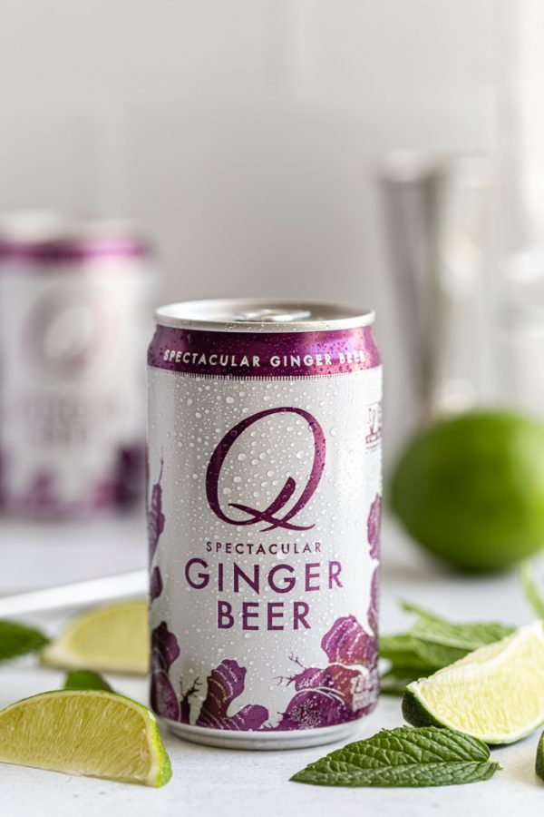 up close shot of a can of Q mixers ginger beer. with lime wedges and mint all around