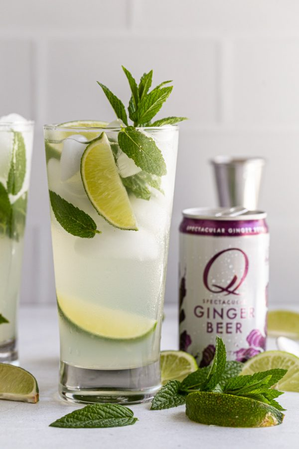 mojito with a can of Q ginger beer next to it. with lime wedges and mint all around
