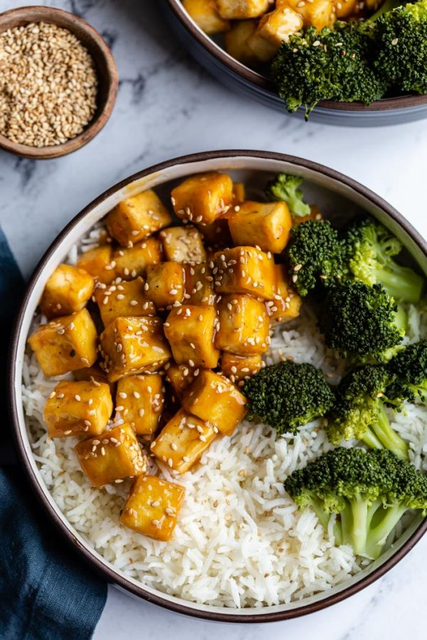 top down shot of orange sesame tofu cubes on a bed of rice with sauteed broccoli on the side and sprinkled with toasted sesame seeds. Sitting on a marble board with another bowl in the corner and a small bowl of sesame seeds on the side