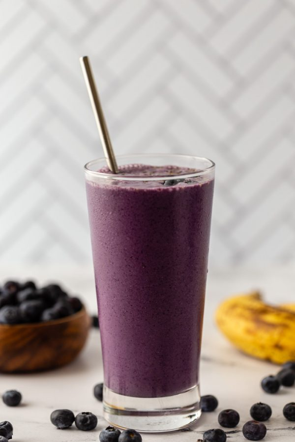 purple blueberry smoothie in a tall glass sitting in front of a tiled backdrop. Fresh blueberries and bananas around the scene
