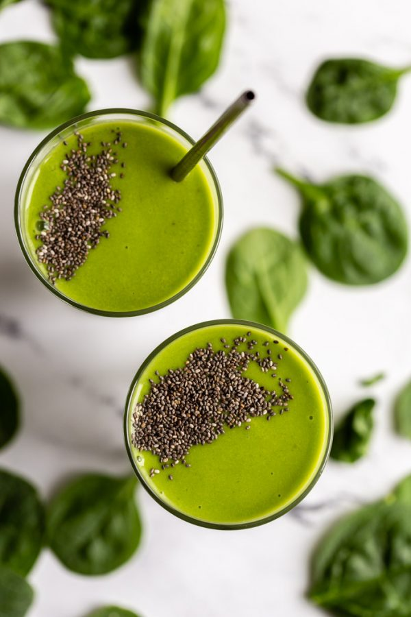 2 glasses filled with green smoothie topped with chia seeds. on a marble board with spinach sprinkled al around