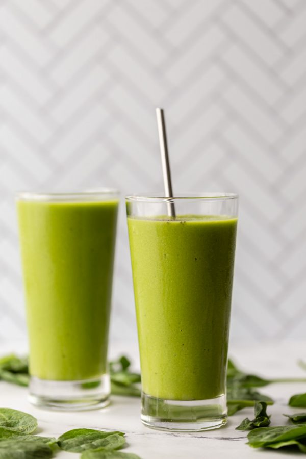 2 glasses filled with green smoothie on a marble board with spinach sprinkled al around