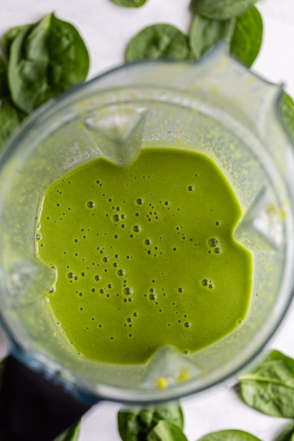 top down shot of a green smoothie inside of a vitamix blender with spinach all around the scene