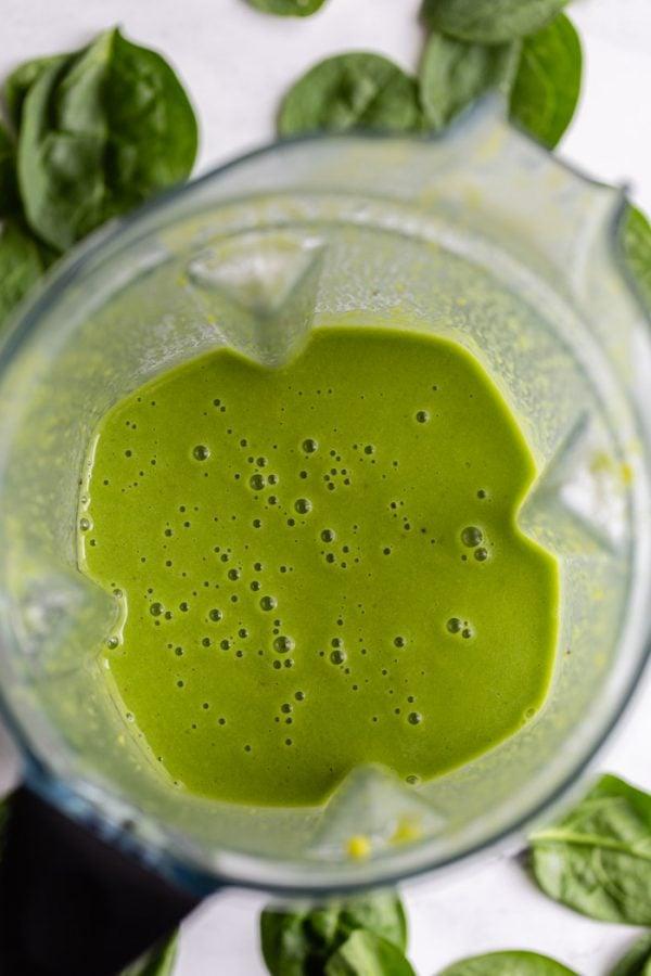 cima para baixo tiro de um smoothie verde dentro de um liquidificador vitamix com espinafre por toda a cena