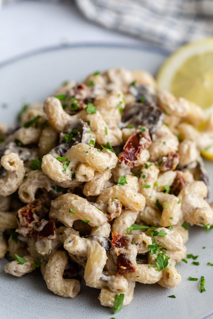 up close shot of a creamy vegan pasta recipe with mushrooms and sun dried tomatoes in it. on a blue plate and topped with parsley