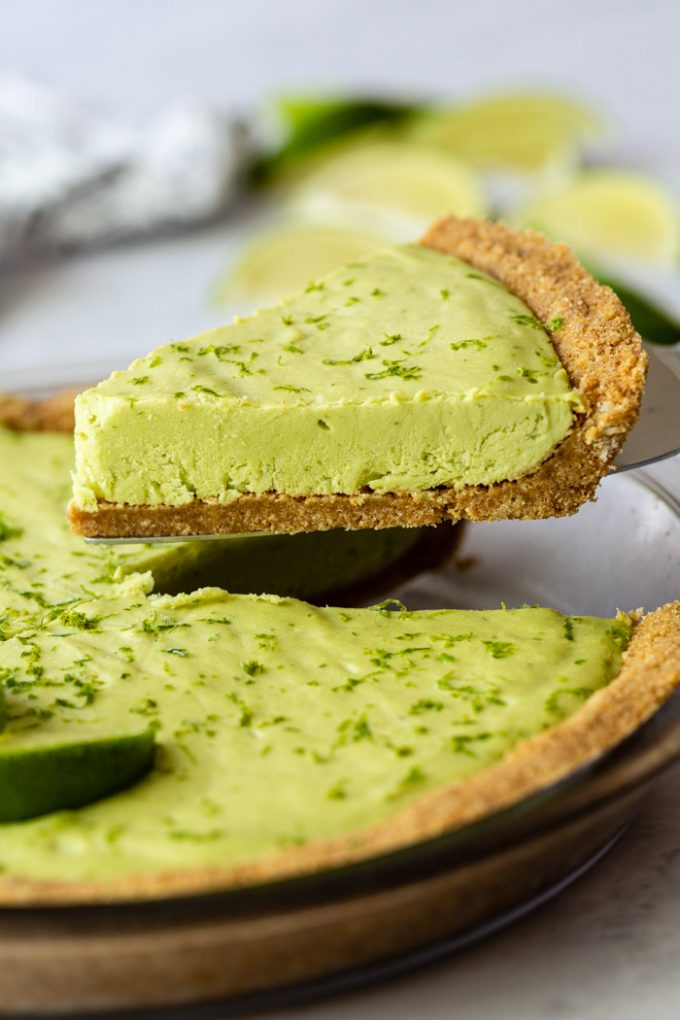 slice of key lime pie being lifted from the whole pie with limes in the background and lime zest all over the pie
