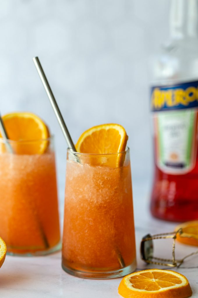 2 frozen aperol spritz cocktails with orange slices in them and a bottle of aperol in the background