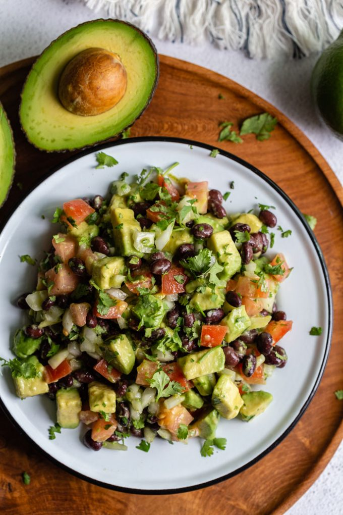 top down shot of a tin bowl filled with avocado and black bean salad with tomato, onion and cilantro mixed in as well. the bowl is sitting on a round wood board with fresh avocado in the corner