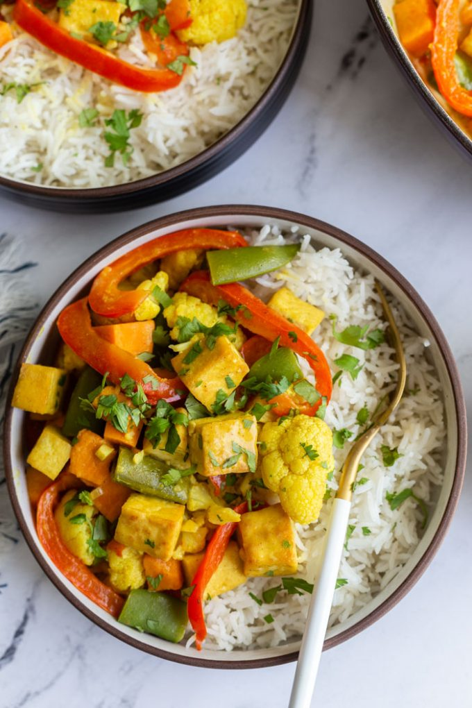 top down shot of a bowl of tofu curry that's yellow in color with red bell pepper, tofu, snap peas, and cilantro served over white rice